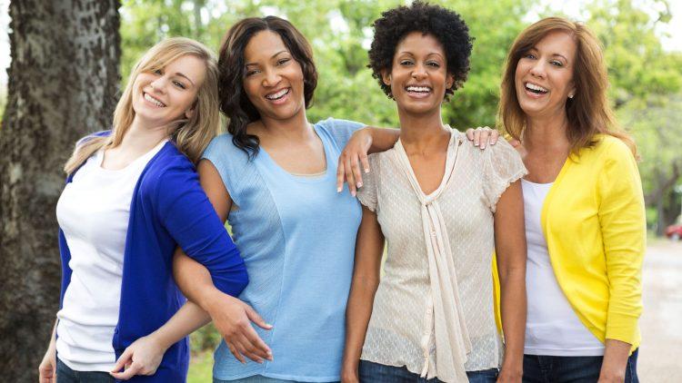 Vier stehende lächende junge Frauen