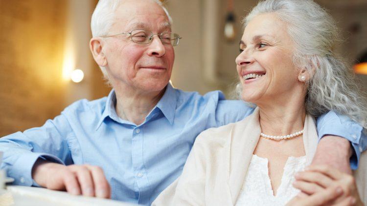 Älteres, zufriedenes Paar lächelt sich an