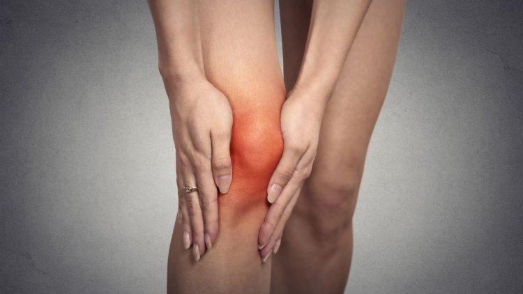 Frau fasst mit beiden Händen an ihr schmerzendes Knie