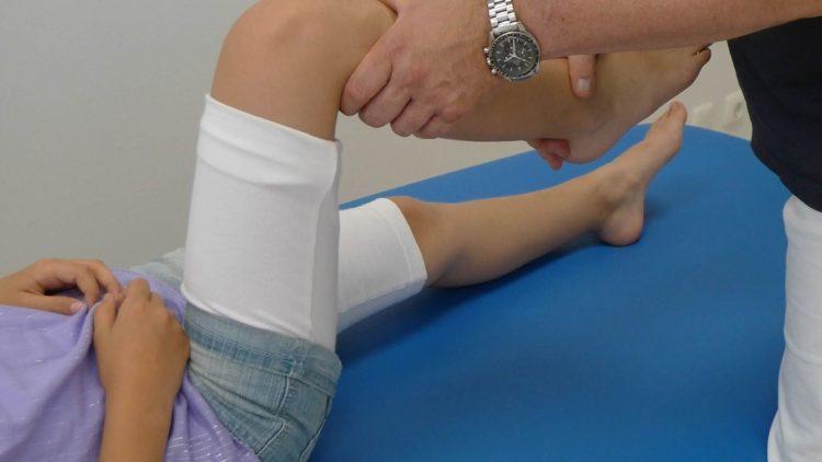Mann bewegt Knie bei einem liegenden Kind