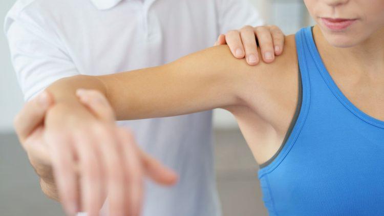 Mann untersucht Schulter bei einer Frau