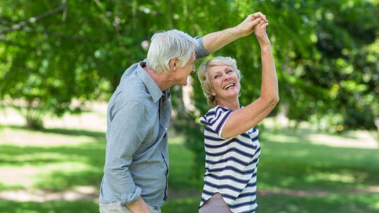 Älteres Paar fasst sich an der Hand mit erhobenem Arm