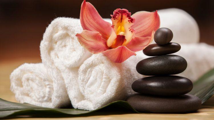 Gerollte Tücher, schwarze flache Steine mit Blume