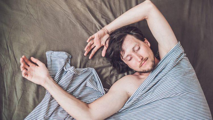 Liegender, schlafender Mann im Bett