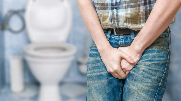 Stehender Mensch hält Hände vor Genitalbereich vor Toilette