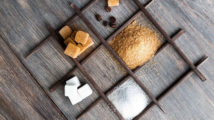 Puder-, Würfelzucker und Schokolade in Holzfächern