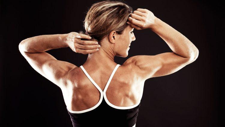 Sportlerin mit Sport-BH fasst sich an den Nacken