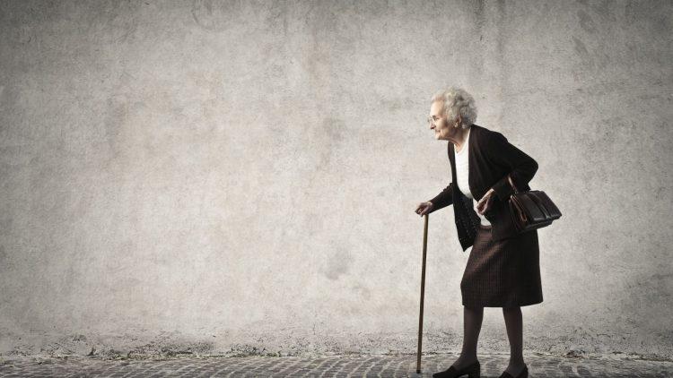 Ältere gebückte Frau mit Gehstock