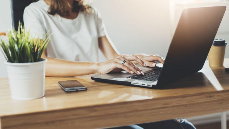 Sitzende Frau tippt auf einem Laptop