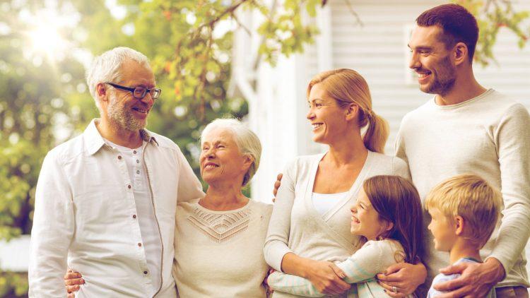Drei Generationen stehen gemeinsam im warmen Abendlicht