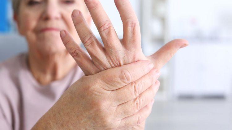 Ältere Frau fasst sich an der Hand