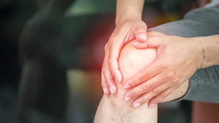 Mensch fasst sich mit beiden Händen am Knie