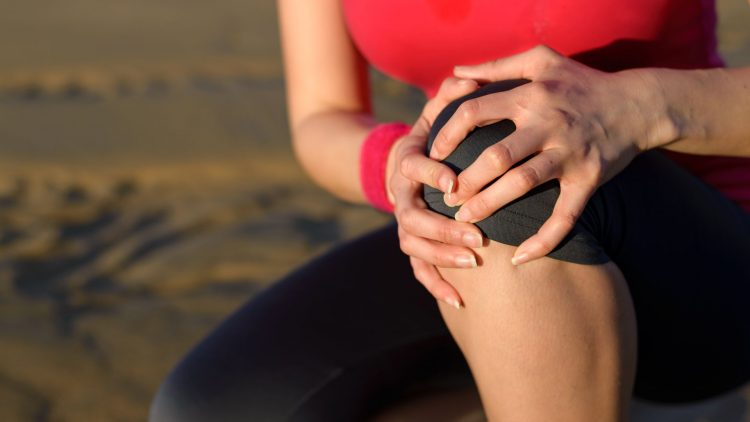 Frau hält sich das linke Knie mit beiden Händen