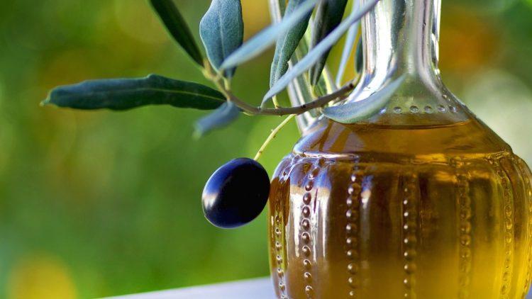 Krug mit Olivenöl mit Olivenzweig