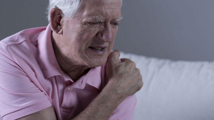 Älterer Mann fasst sich an die Schulter