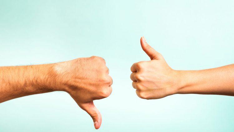 Zwei Hände jeweils mit Daumen nach oben und nach unten