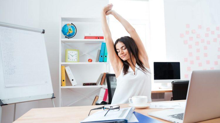 Junge Frau streckt die Arme hoch, sitzend im Büro