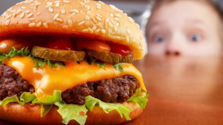Kind schaut auf Hamburger