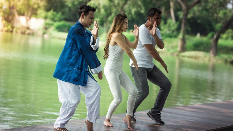 Zwei Männer und eine Frau beim Tai Chi