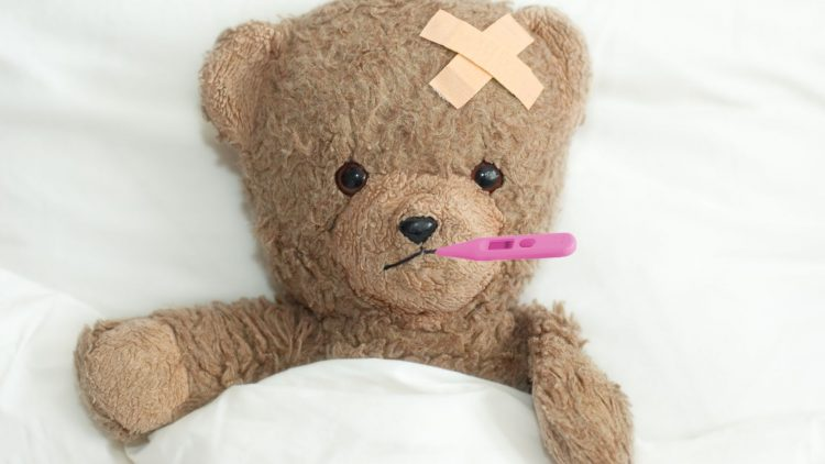 Teddy Bär mit Thermometer im Mund im Bett