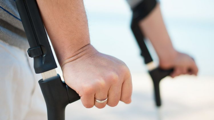 Zwei Hände gestützt auf Unterarmgehstützen