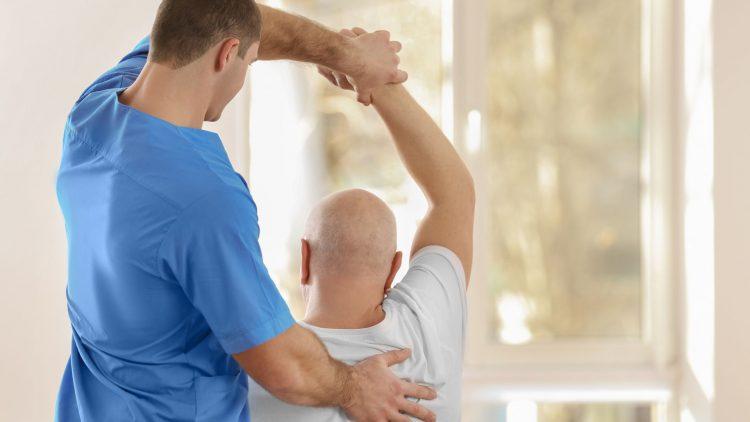 Therapeut hält Arm eines Patienten hoch