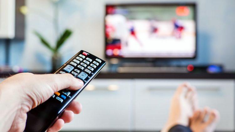 Hand mit Fernsteuerung und Fernseh