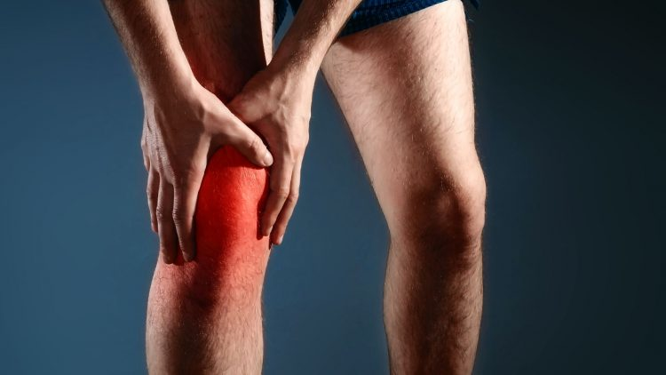 Mann hält sich schmerzhaftes Knie mit beiden Händen