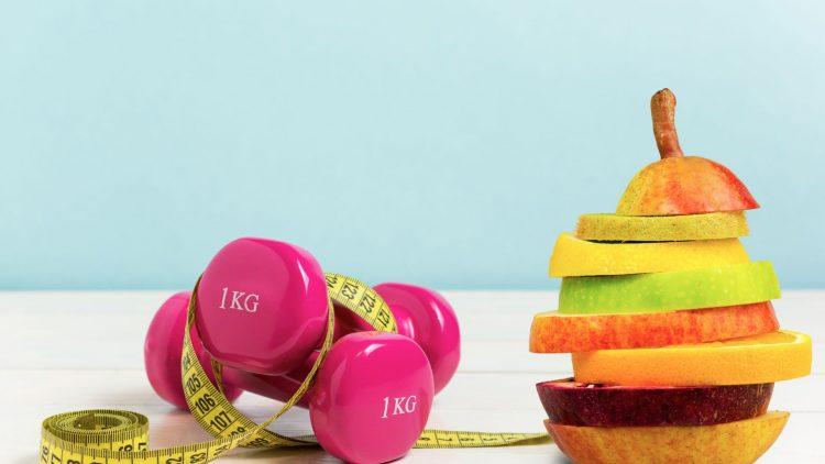 Obststücke, Hanteln und Messband auf einem Tisch