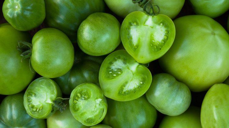 Mehrere grüne Tomaten und Tomatenhälften