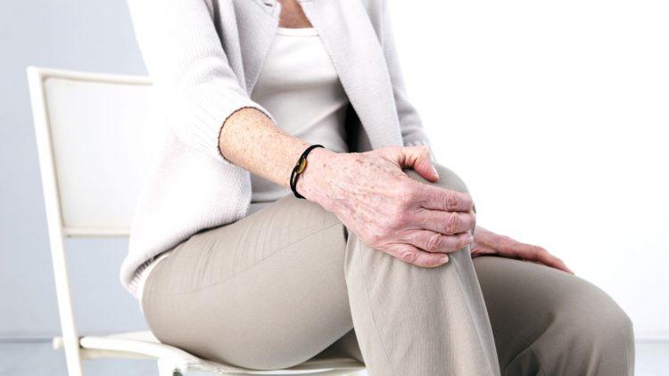 Frau hält sich das Kniegelenk