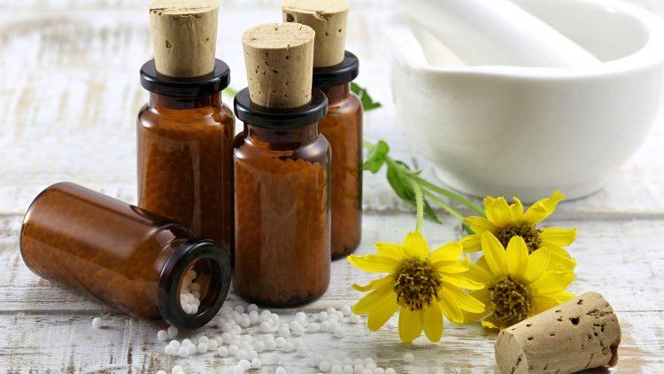 Arnikablumen und braune Medikamentenbehälter auf einem Tisch