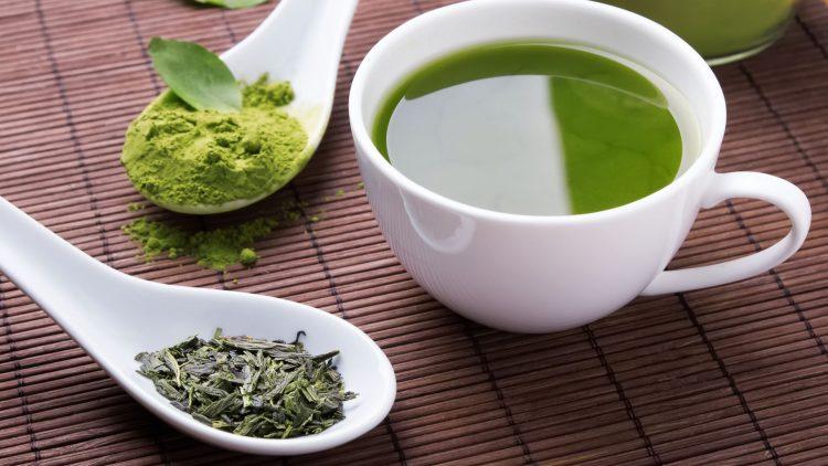 Weiße Tasse mit Grüntee, Grünteepulver in weißem Löffel