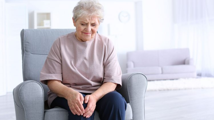 Ältere sitzende Frau hält sich das Knie mit beiden Händen