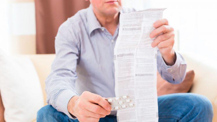 Sitzender Mann mit Beipackzettel und Blister in der Hand
