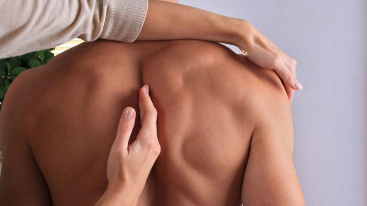 Frau manipuliert nackten Rücken eines Patienten