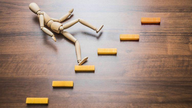 Holzmodell eines Menschen stürzt auf einer Modelltreppe