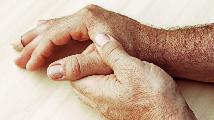 Mensch fasst sich den Daumen mit der Hand