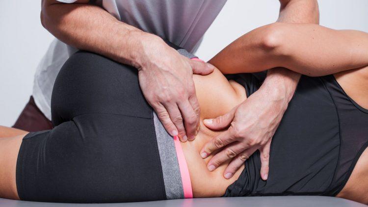 Mann manipuliert Lendenwirbelsäule bei einem Patienten