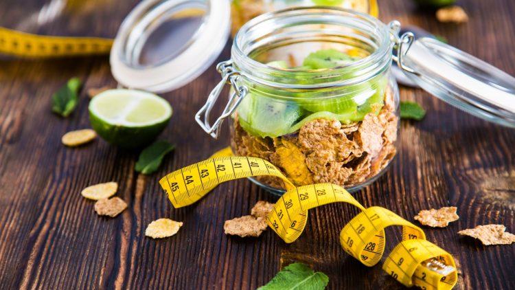 Maßband und Nahrungsmittel in einem Glas