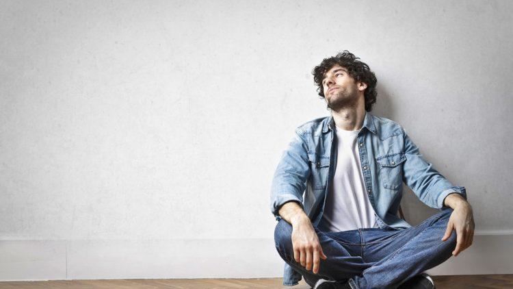 Ein Mann sitzt, angelehnt gegen eine Wand