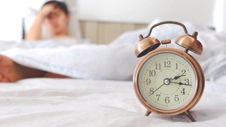 Wecker vor einem im Bett liegenden Mann