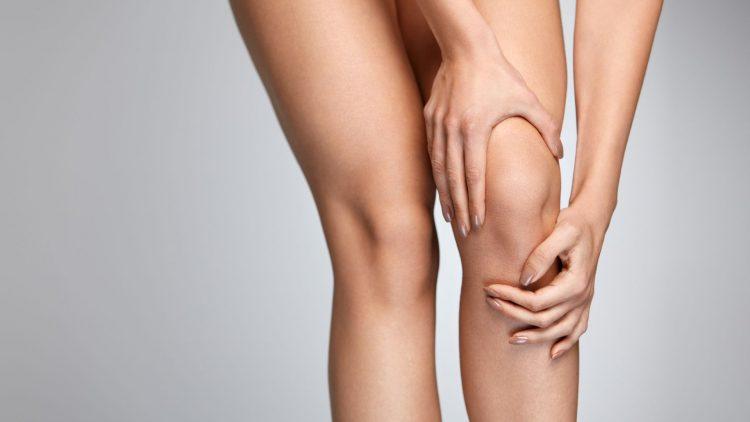 Frau fasst sich mit beiden Händen ans Knie