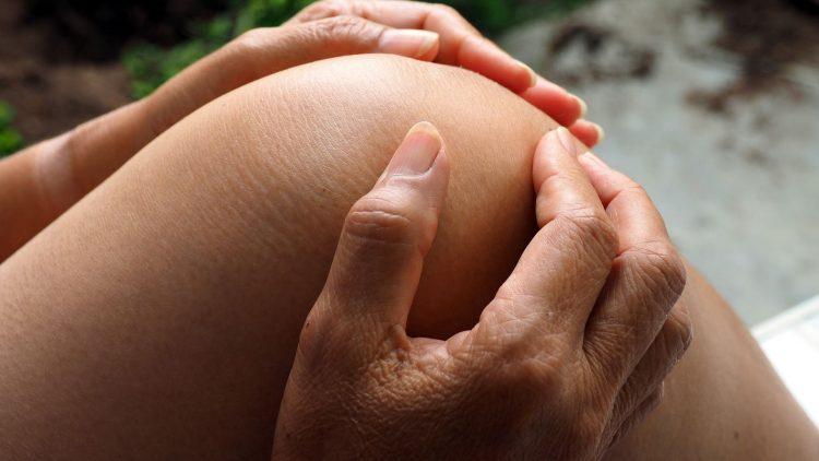 Mensch fasst sich mit beiden Händen ans Knie