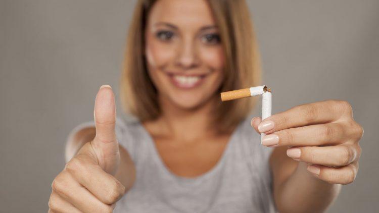 Junge Frau hält gebrochene Zigarette in der Hand