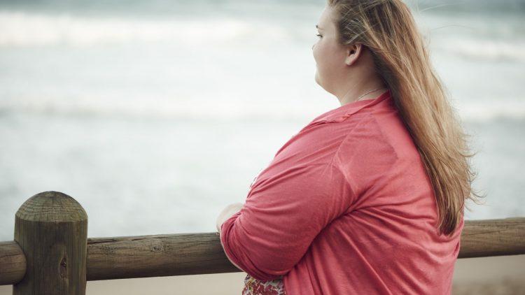 Übergewichtige junge Frau schaut aufs Meer