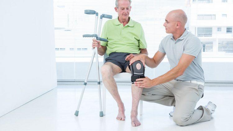 Mann fasst das Knie eines sitzenden Patienten an