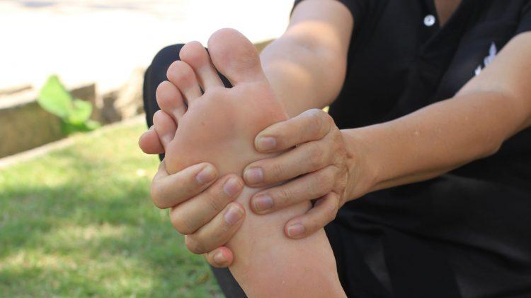 Frau hält ihren rechten Fßs mit zwei Händen