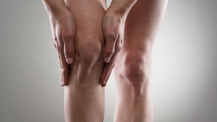 Mann fasst sich mit beiden Händen am Knie
