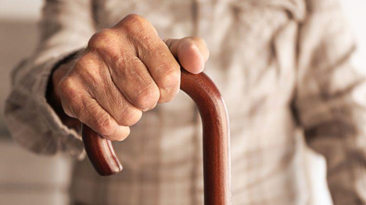 Hand hält einen Gehstock